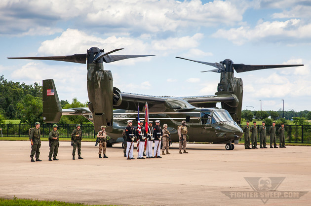 A Marine color guard stands in front of the CH-46's replacement, the MV-22B Osprey