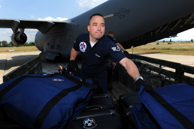 Staff Sgt. Jacob Richmond, a public affairs community relations specialist, unloads luggage bags near the C-17 Globemaster, in preparation to depart Graf Ignatievo Air Base, Bulgaria for RAF Waddington, U.K. June 28, 2011. The Thunderbirds will perform in nine countries during their six-week European tour, fostering international goodwill and representing America's Airmen around the globe. (U.S. Air Force photo/Staff Sgt. Larry E. Reid Jr., Released)
