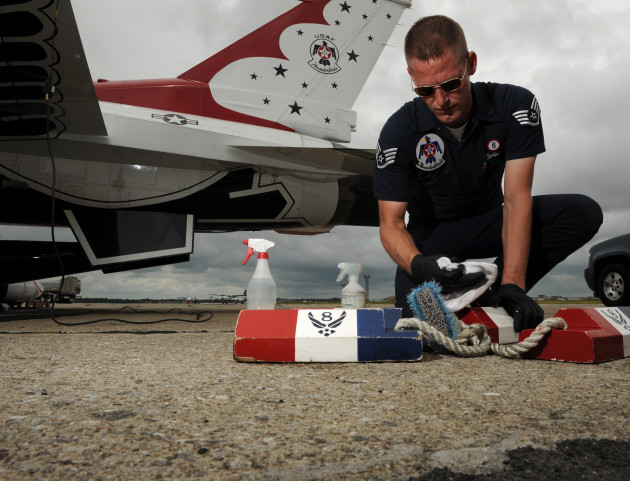Staff Sgt. Andrew Hartman, Thunderbird 8 assistant dedicated crew chief, wipes down the chocks to his jet at Cleveland Hopkins Airport, Cleveland, OH, Sept. 5, 2011. (U.S. Air Force photo/Staff Sgt. Larry E. Reid Jr., Released)