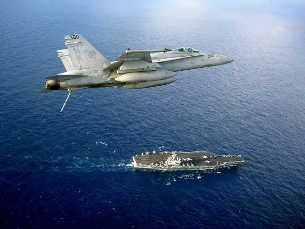 """An F/A-18C Hornet assigned to the """"Stingers"""" of Strike Fighter Squadron 113 flies above the Nimitz-class aircraft carrier USS Ronald Reagan before a final approach to make an arrested landing. The Ronald Reagan Carrier Strike Group is on a routine deployment in the U.S. 7th Fleet area of responsibility."""
