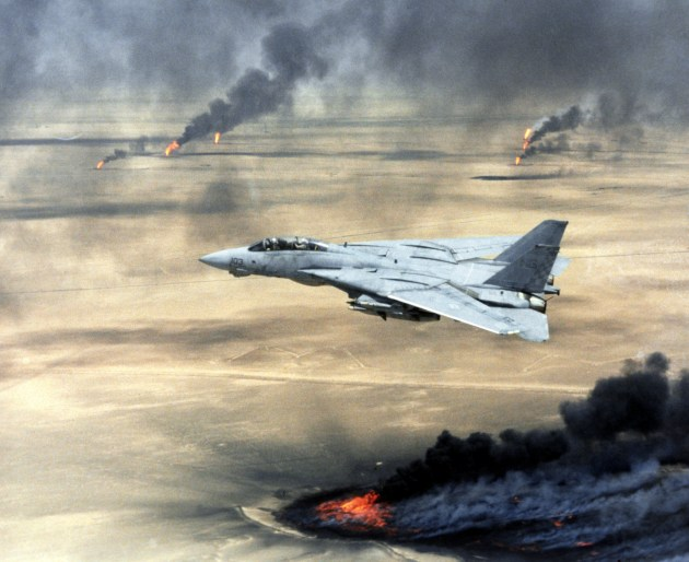 US Navy (USN) F-14A Tomcat, Fighter Squadron 211 (VF-211), Naval Air Station (NAS) Oceana, Virginia Beach, Virginia (VA), in flight over burning Kuwaiti oil wells during Operation DESERT STORM.