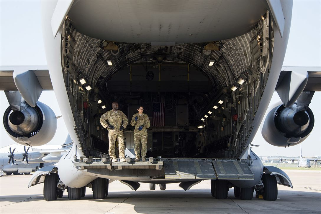 Air Force Tech Sgt Milton Knight and Senior Airman Courtney Johnson stand in the back of a C-17 Globemaster III Naval Air Station Joint Reserve Base Fort Worth Texas