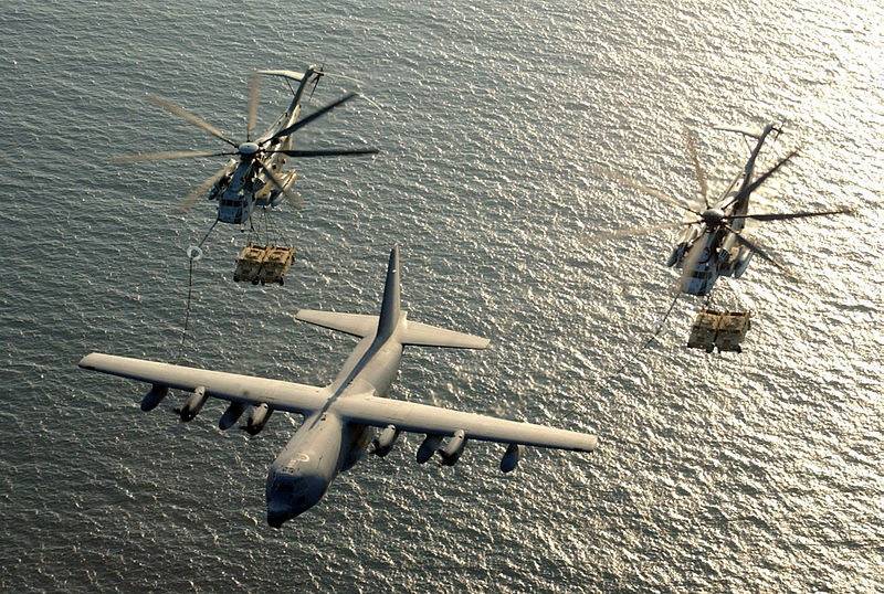 Two U.S. Marine Corps CH-53E Super Stallion helicopters refueling helicopters towing humvee