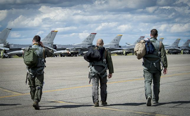 U.S. Air Force fighter pilots assigned to the 14th Fighter Squadron walk onto the flight line during RED FLAG-Alaska