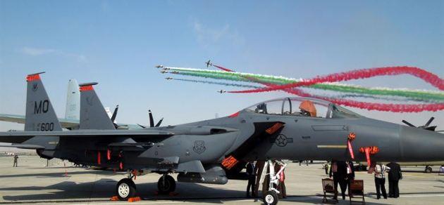 Al Fursan The Knights the United Arab Emirates Air Force aerobatic display team, flies in formation behind a U.S. Air Force F-15E Strike Eagle