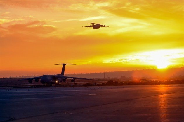 Air Force C-5M Super Galaxy from the 22nd Airlift Squadron lands as a C-17 Globemaster III takes off at Marine Corps Air Station Miramar, Calif