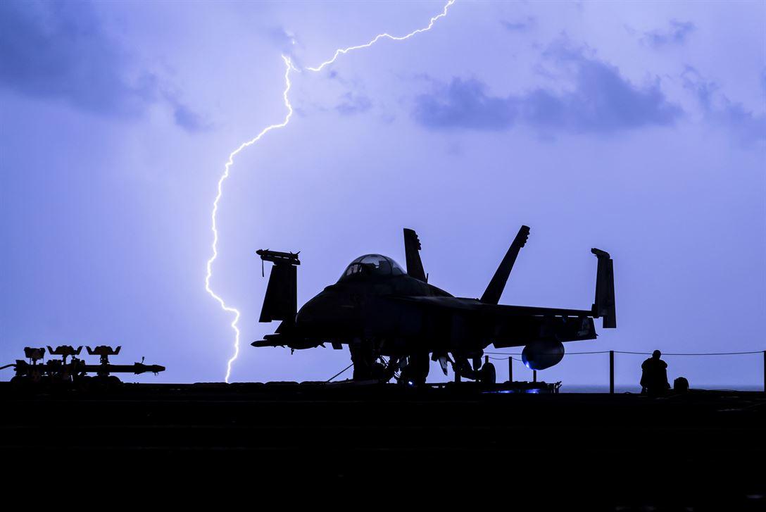 Lightning strikes near the aircraft carrier USS Theodore Roosevelt F-18 hornet