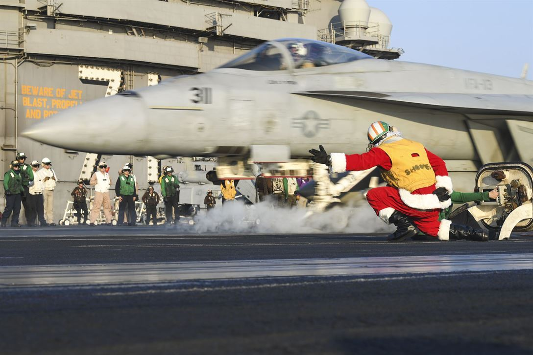 Navy Lt. Larry Young, dressed as Santa Claus, signals to launch an F/A-18 E Super Hornet on the flight deck of the USS Theodore Roosevelt