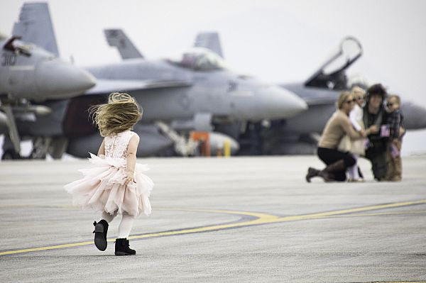 young girl runs to greet her family after the arrival of Strike Fighter Squadron (VFA) 115