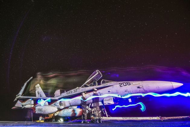 Marines move an F/A-18C Hornet on the flight deck of the USS Theodore Roosevelt