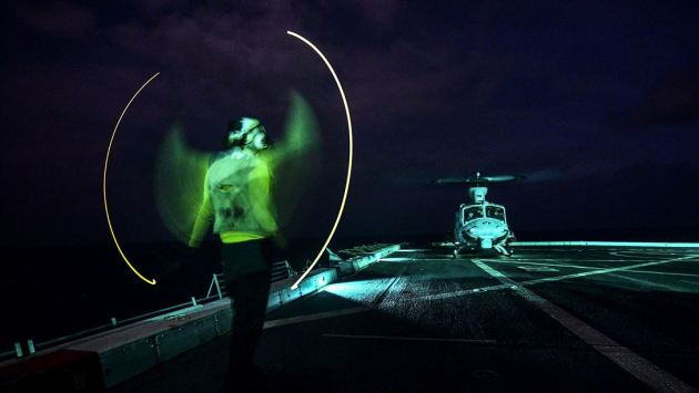 Navy Seaman Ryan Sharland directs a UH-1Y Venom helicopter on the flight deck of the USS San Diego