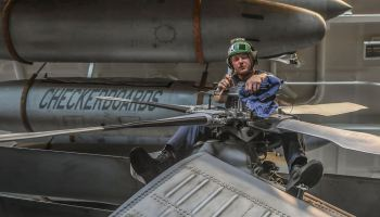 Petty Officer 3rd Class Thurman Bailey cleans and tightens the rear rotor on an MH-60R Seahawk helicopter