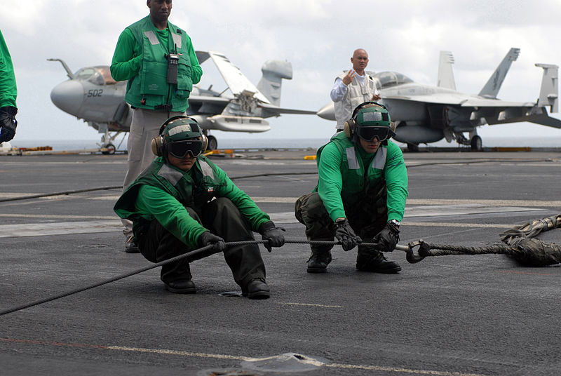 Two flight deck personnel aboard the Nimitz-class aircraft carrier USS Ronald Reagan (CVN 76) stretch an arresting gear cable connected to a barricade net during a flight deck drill