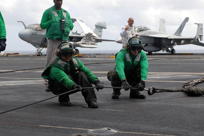 Two flight deck personnel aboard the Nimitz-class aircraft carrier USS Ronald Reagan (CVN 76) stretch an arresting gear cable connected to a barricade net during a flight deck drill