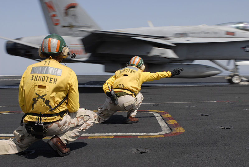 Flight deck officers, referred to as shooters, launch an F/A-18C Hornet