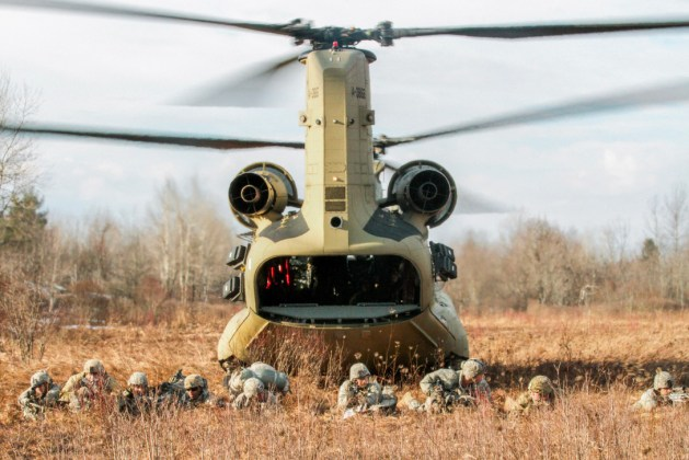 Soldiers take up defensive positions after disembarking from a CH-47 Chinook helicopter