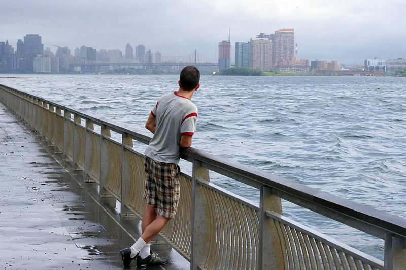 A man looks out at the swollen East River in East River Park in Manhattan after Hurricane Irene helicopter crash
