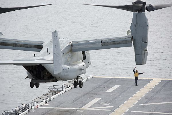 Aviation Boatswain's Mate 2nd Class Jamel Agee signals an MV-22 Osprey