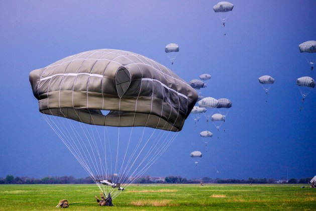 U.S., Italian and Polish paratroopers descend after jumping from an Air Force C-130 Hercules aircraft at Juliet drop zone in Pordenone, Italy