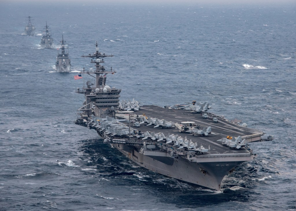 An American aircraft carrier transits in formation with Japan Maritime Self-Defense Force Destroyers