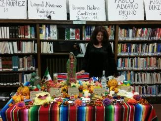 Elena Herrada stands at an ofrenda honoring five men whose lives were unfairly taken from them by their employer.
