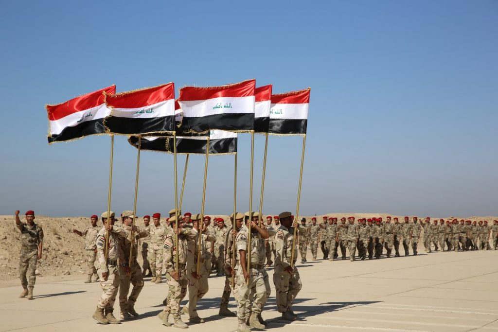 Members of the Popular Mobilization Program march in formation with Iraqi national flags during a graduation ceremony at Al Taqaddum Air Base with US equipment and personnel