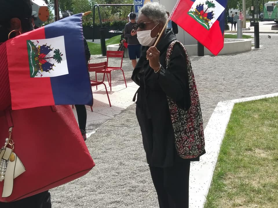 Detroit press conference in solidarity with Haiti migrants with Dr. Gloria House holding national flag, Sept. 26, 2021