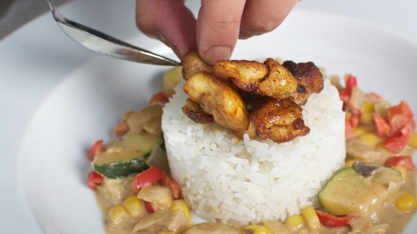Gebakken kip met rijst en groente in een heerlijke kokossaus