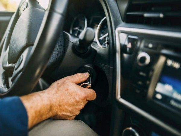 a hand putting key in ignition switch