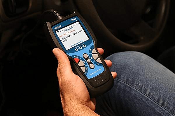 A man using a car diagnostic tool to check the engine problems