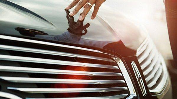 a hand touching the car paint