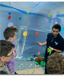 High School student teaching inside the coral reef biome.
