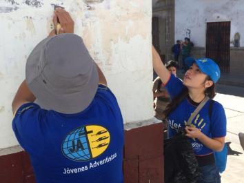 Jóvenes limpian pared del centro histórico para luego ser pintada.