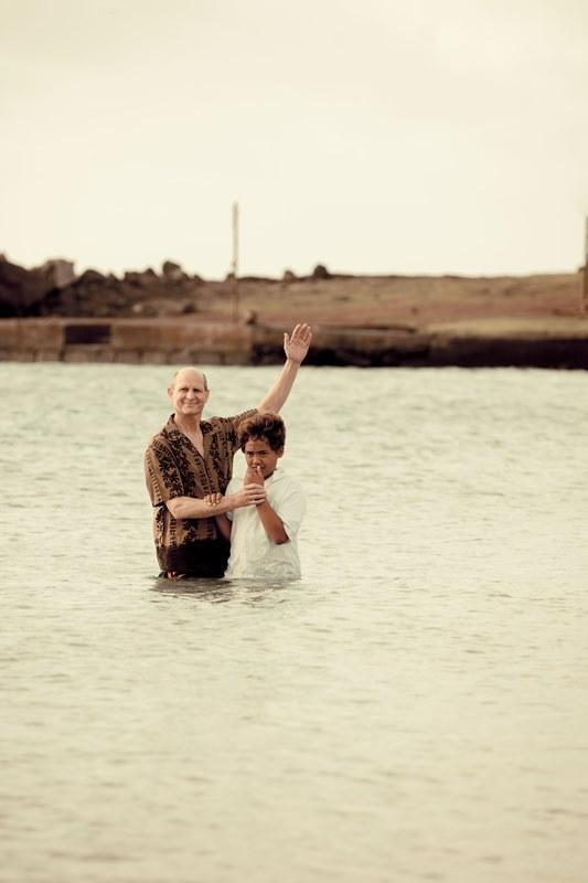 Pr. Wilson bautizando a uno de los niños natiivos de isla. Crédito: Alfred Müller