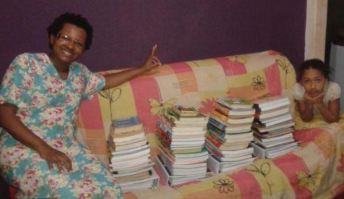 Ana Paula e a filha junto com os livros doados para o colégio.