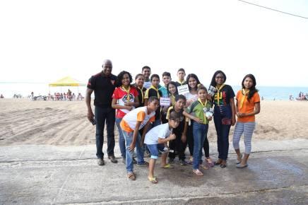Jovens distribuem materiais gráficos nas areias da praia em Outeiro