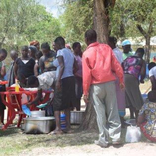 Pessoas recebem uma refeição gratuita em uma clínica em Kibos, Quênia