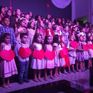 Crianças cantando para as mães