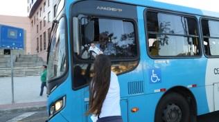 Estudante entrega sacola a motorista de ônibus