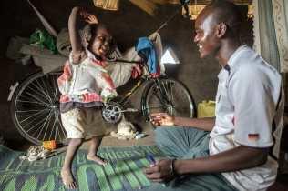 Pai e criança refugiados brincam em acampamento