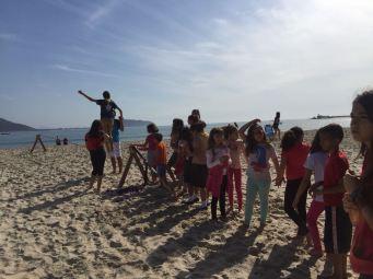 Voluntários auxiliam crianças a se equilibrarem no esporte slackline. [Foto: Felipe Silva].