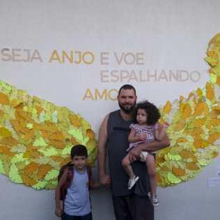 Arthur Maximus com o pai e a irmã posam para foto nas asas amarelas.