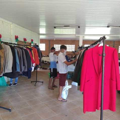 Famílias escolhem roupas disponibilizadas pela ASA.[Foto: Reprodução].