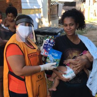 Sandra Sobral realizando entrega de leite e chocolate na comunidade Pq. Vila Nova, em Duque de Caxias. (Foto: divulgação)