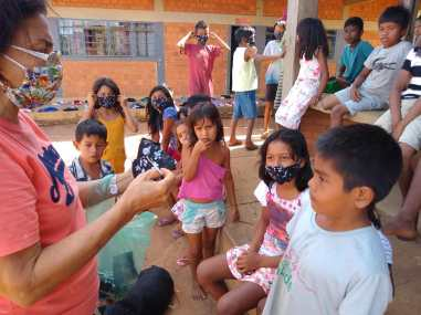 Juntamente com calebes professora Iraci distribui máscaras para as crianças da aldeia xerente