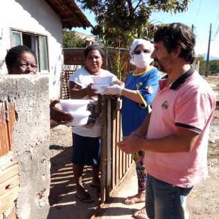 Voluntária entrega marmita em residência de família carente (Foto: Divulgação)