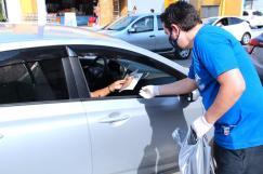 Pastor Roberto Albuquerque, líder de publicações, entrega livro para ocupantes de veículo (Foto: Renan Lima)