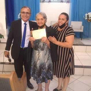 Idoda recebendo seu certificado após o batismo. [Foto: Arquivo de familiares].