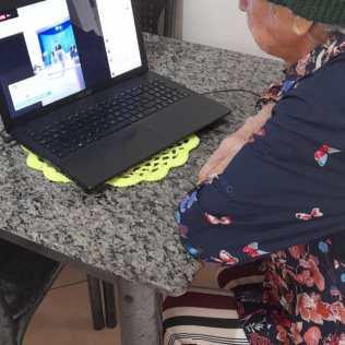 Dona Irma assistindo culto da Igreja Adventista pela internet. [Foto: Arquivo de familiares].