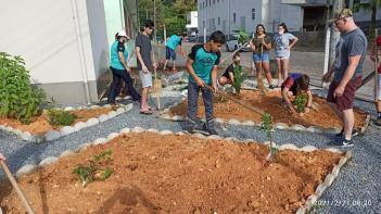 Jovens revitalizando canteiro no pátio da Secretaria de Saúde de Benedito Novo. [Foto: Reprodução].